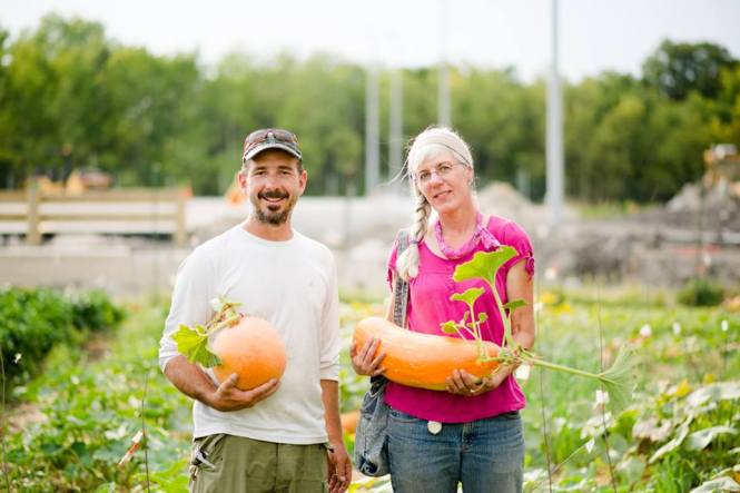 Kenton Lobe and Caroline Chartrand holding Arikara and Gete Okosomin squash that were seed saved at the CMU Farm in 2013.